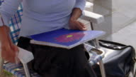 Tilt down tilt up medium shot artist sitting in chair / painting flower and using palette before looking up / Venice Beach