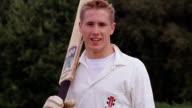 tilt down tilt up PORTRAIT cricket player holding bat on shoulder + smiling / Herfordshire, England
