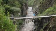 Tilt down to male hiker crossing suspension bridge