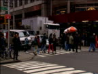 Tilt down to New Yorkers crossing roads using zebra crossings and yellow cabs zoom past pedestrians walk in both directions on busy sidewalk