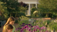 Tilt down to two girls smelling irises in a garden.