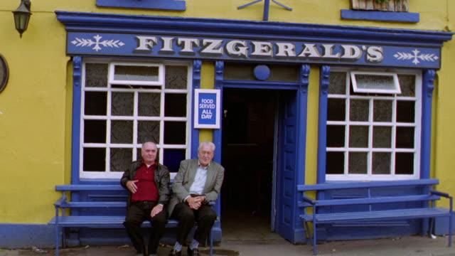 tilt down PAN two senior men sitting on bench in front of 'Fitzgerald's' pub / Avoca, Ireland