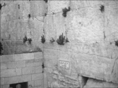 B/W 1967 tilt down Wailing Wall to crowd gathered to celebrate after Six Day War / Jerusalem / newsreel