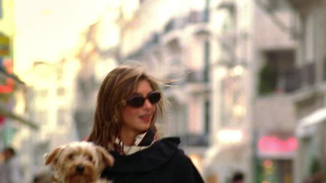 Tilt down woman walking on street carrying small dog / Paris, France