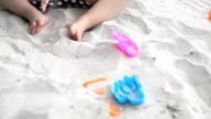 Tilt shot cute girl playing sand on the beach