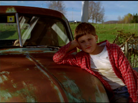 Tilt up and zoom out over boy in red checked shirt leaning on bonnet of rusty pickup, Vermont