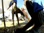 Tilt up as young boy hammers stick into ground as he attempts to build shelter following devastating earthquake Haiti 14 January 2010