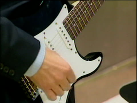 Tilt up British Prime Minister Tony Blair playing electric guitar Feb 03