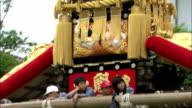 Tilt up children on miniature shrine, Japan