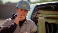 Tilt up construction worker holding coffee and eating doughnut /  Phoenix, Arizona
