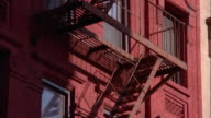 Tilt up fire escapes to cornice on brick building facades / NYC