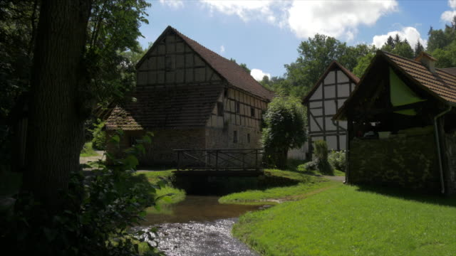 tilt up, flowing stream and bridge with half timbered farm houses
