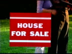 Tilt up from a House For Sale sign to a real estate agent talking with an interested family.