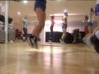 Tilt up from feet of aerobics class exercising wearing leotards leggings and eighties style sportswear