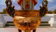 tilt up from golden ornate incense burner pot in foreground to golden temple in background