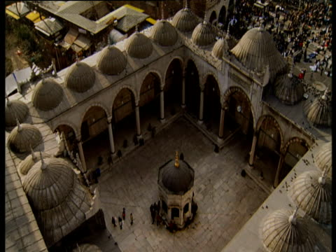 Tilt up from ornate courtyard with domes and arches to city and mosques in background Istanbul