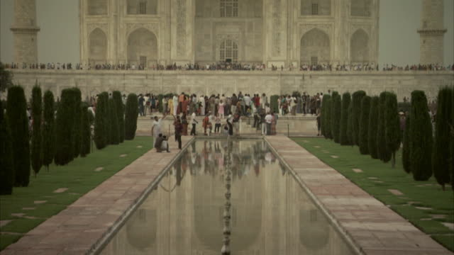 Tilt up from reflections to the top of the Taj Mahal, India.
