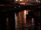Tilt up from rippling water to boats moored in harbour at night zoom out to La Garde Hill in the Old Port of Marseilles