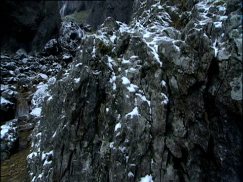 Tilt up from snow covered rocks to steam running through Gordale Scar Yorkshire
