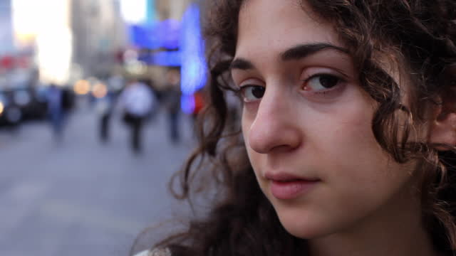 Tilt up from sweater to profile young woman's face on NYC sidewalk   turns eyes to look at camera