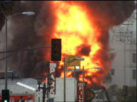 tilt up from traffic to burning building in background / Los Angeles riots