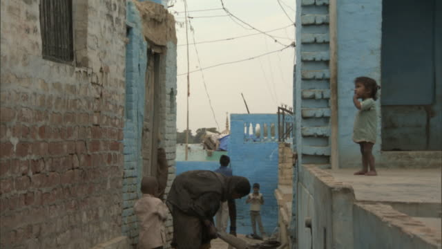 Tilt up from woman with children in alleyway to rhesus macaque leaping over rooftops, Bateshwar Available in HD.