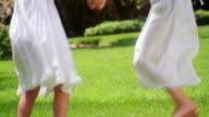 tilt up MS girl + blonde girl holding hands + spinning on grass laughing