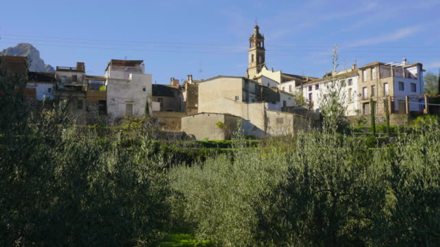 tilt up, green terraces in front of white houses and church steeple of Benialí village