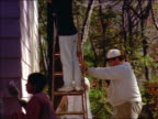 tilt up group of people + women on ladders painting small house exterior lavender