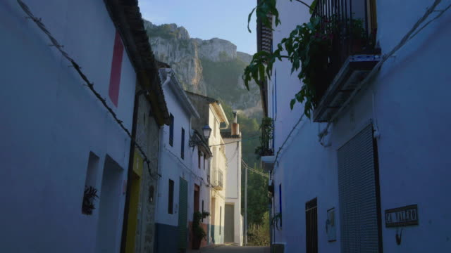 tilt up, houses in steep narrow street with mountains in background