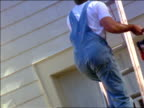 REAR VIEW tilt up man climbing ladder carrying paint can + brush to top of house