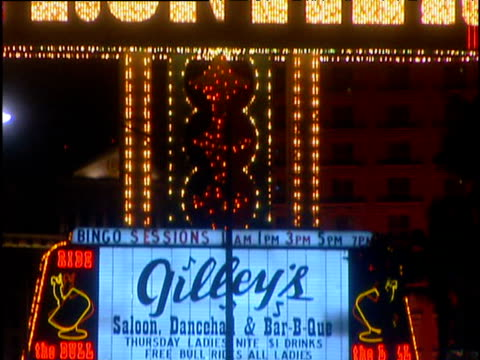 Tilt up neon sign for tourist locations with blue yellow and red lights Las Vegas