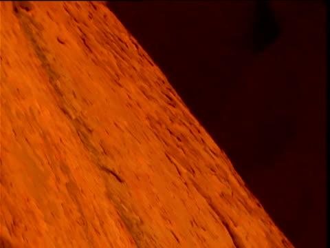 Tilt up over glowing red sandstone of Uluru to grey sky above, Northern Territory, Australia