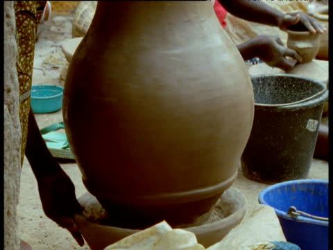 Tilt up pot being finished on potter's wheel, Djenne