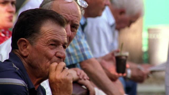 tilt up rack focus PROFILE group of senior Italian men sitting outdoors / Milan, Italy