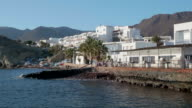 tilt up, sea in front of restaurant terrace and white houses along shore