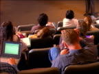 REAR VIEW tilt up student typing on laptop computer tilt up male professor talking at front of lecture hall