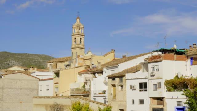 tilt up, sunlight on back of houses and church steeple in village of Benissivà
