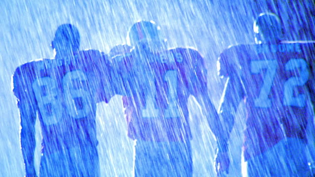 BLUE OVEREXPOSED MS tilt up three football players walking away from camera in rain