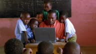 MS tilt up tilt down Black man sitting + using computer in classroom with children surrounding him / Kenya