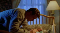tilt up tilt down man putting sleeping baby into crib in nursery / man turning off light + looking down at baby