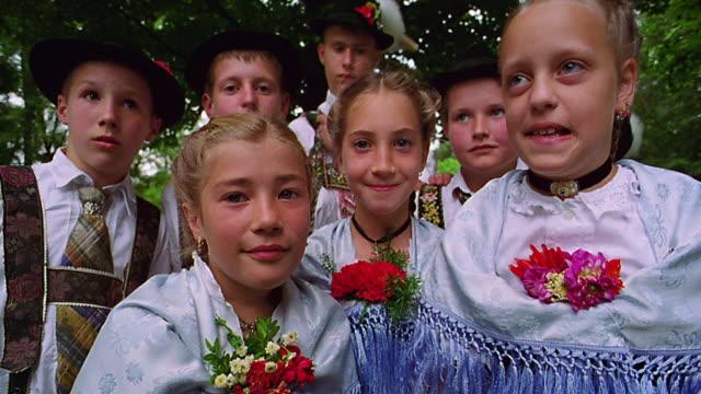 tilt up tilt down PORTRAIT group of children in German costumes smiling / tree in background / Bad Kohlgrub, Bavaria