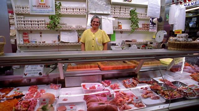 tilt up tilt down PAN PORTRAIT smiling senior female butcher standing behind counter in shop / Florence, Italy
