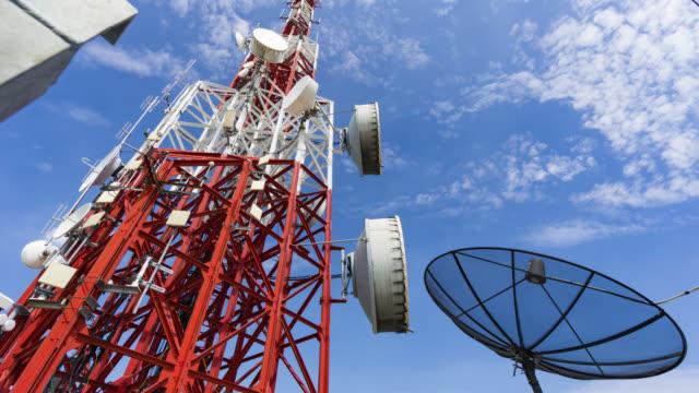 Kantelen van timelapse toren van communicatie met een heleboel verschillende antennes onder de blauwe lucht en de wolken