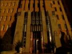 Tilt up to top of Amazon.com's orange brick building headquarters under clear blue sky
