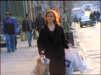 tilt up woman carrying shopping bags on NYC sidewalk walking towards camera
