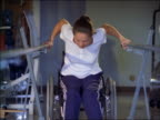 tilt up woman in wheelchair standing up + walking while holding onto bars in gym / smiles