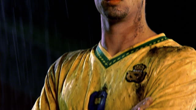 tilt up zoom in soccer player wearing muddy yellow uniform standing w/arms folded