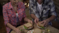 Tilt view of couple at a cottage eating a sandwich