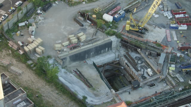 Tilt-down shot to the entry point shaft at the East Side Access work site with walking workers
